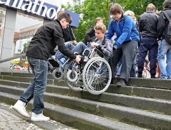 No es la solución. Fotografía de dos jóvenes cargando a un compañero en silla de ruedas para subir unas escaleras